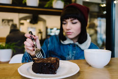 Beautiful young hipster girl eating dessert and drinking coffee in a nice cafe Royalty Free Stock Images