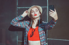 Beautiful young hipster girl in the hat taking picture of hersel Stock Photos
