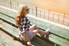 Beautiful young hipster girl sitting on the bench Stock Photography