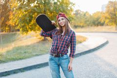 Beautiful young hipster girl in stylish clothes holding a skateb Stock Images