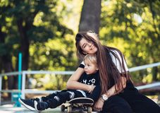 Beautiful young hipster mom and little son at the skatepark royalty free stock photography