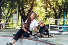 Beautiful young hipster mom and little son at the skatepark. Beautiful young hipster mom and little son have fun at the skatepark royalty free stock photo