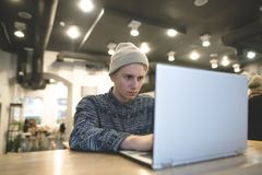 The beautiful young hipster uses the internet on a laptop in a cozy cafe. A student works on a computer in a cafe. The beautiful young hipster uses the internet Stock Photography