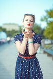 Beautiful young hipster woman in fifties style sending kiss Royalty Free Stock Photo