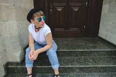 Beautiful young hipster woman posing sitting on stairs stock photos