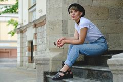 Beautiful young hipster woman posing sitting on stairs royalty free stock image