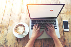Beautiful young hipster woman`s hands busy working on her laptop sitting at wooden table in a coffee shop Stock Images