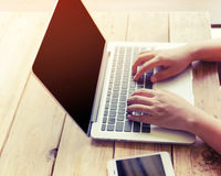 beautiful young hipster woman`s hands busy working on her laptop sitting at wooden table in a coffee shop Stock Photo