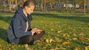 Girl autumn in the park sits on the grass, sending sms from the phone. Beautiful young hipster woman using smart phone at autumn park. Pretty young woman in stock footage