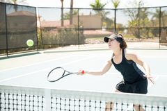 Female tennis player practising hard. Beautiful young hispanic female player hitting the tennis ball on court, practising on a summer day Royalty Free Stock Photos