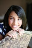 Beautiful young hispanic girl. Pretty preteen ethnic girl sitting in chair Royalty Free Stock Photo