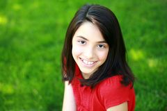 Beautiful young hispanic girl smiling. Pretty preteen ethnic girl sitting in grass Royalty Free Stock Photo