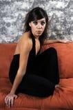 Beautiful young hispanic woman. Crouching on a sofa Stock Photos