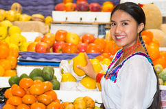 Beautiful young hispanic woman wearing andean traditional blouse picking up papaya for camera inside fruit market Royalty Free Stock Images