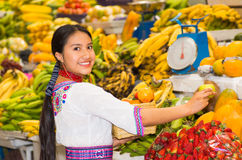 Beautiful young hispanic woman wearing andean traditional blouse posing for camera holding some fruits and smiling Stock Image