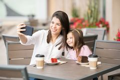 Mother and daughter taking selfie at cafe Royalty Free Stock Photo