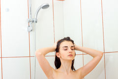 Beautiful young hot girl closed her eyes and washes the hair under the shower Royalty Free Stock Photo
