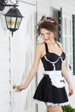Beautiful young housemaid holds on to front door handle Royalty Free Stock Photo