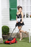 Beautiful young housemaid poses with lawn mower Stock Images
