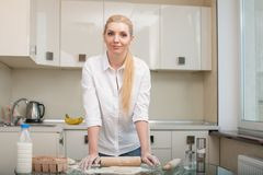 Beautiful young housewife is baking in kitchen Stock Image