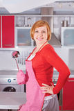 Beautiful young housewife in kitchen holding ladle Royalty Free Stock Photos