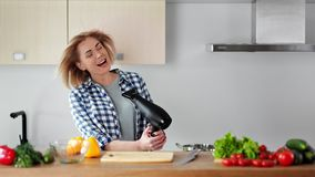 Beautiful young housewife singing song and dancing during drying hair with blow dryer at kitchen. Medium shot cheerful pretty female having fun at modern stock video