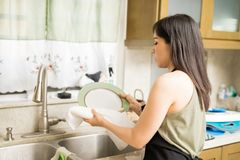 Focused house maid drying utensils with napkin. Beautiful young housewife wiping utensils with towel Stock Image