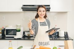 Beautiful young housewife woman with tablet computer cooking in Stock Photos