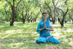 Beautiful young indian woman dressed in a sari praying and meditating in the park hinduism religion yoga. Beautiful young woman dressed in a sari praying and stock photos
