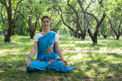 Beautiful young indian woman dressed in a sari praying and meditating in the park hinduism religion yoga. Beautiful young woman dressed in a sari praying and royalty free stock image
