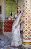 Beautiful young indian woman in traditional clothing with bridal. Makeup and oriental jewelry. Beautiful Girl bollywood dancer in Sari posing outdoor near the Royalty Free Stock Photos