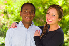 Beautiful young interracial couple in garden environment, embracing and smiling happily to camera Stock Images