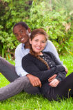 Beautiful young interracial couple in sitting garden environment, embracing and smiling happily to camera Stock Images