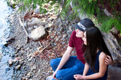 Beautiful young interracial couple sitting together by lake shor Stock Photos