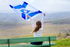 Israeli jewish little girl with Israel flag back view. Beautiful young jewish girl sitting holding Israel flag in the wind and enjoying great view landscape on stock image