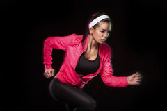 Beautiful young jogging woman. Isolated over black background (colored, retouched) stock photo