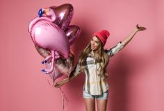 Beautiful young joyful girl is holding a bunch of pink balloons on a pink pastel background. royalty free stock photos