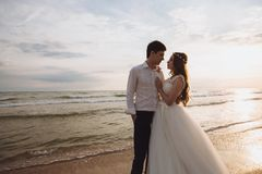 Beautiful young just marriied couple standing on ocean beach. Newlyweds spend time together, embrace and kiss stock photos