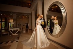 Beautiful young just merried couple posing in front of a large mirror Stock Photography