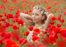Beautiful young kid in red poppy field Stock Photos