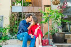Beautiful young kissing couple sitting on the stairs on mediterranean city street. Love, dating, romance, joy and happiness. Lifes. Tyle and tourism concepts Royalty Free Stock Photos