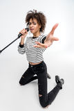 Beautiful young kneeling woman with microphone singing and gesturing isolated on grey Stock Photos