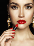 Beautiful young lady apply red lipstick Stock Photos