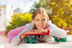 Beautiful young lady with arms on red skateboard Stock Photos