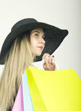Beautiful young lady in a bathing suit, big black hat on high heels, holding colorful bags. Girl goes shopping Stock Photos