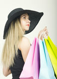 Beautiful young lady in a bathing suit, big black hat on high heels, holding colorful bags. Girl goes shopping Royalty Free Stock Photos