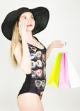 Beautiful young lady in a bathing suit, big black hat on high heels, holding colorful bags and talking on the phone Royalty Free Stock Image