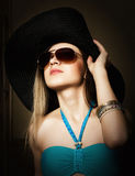 Beautiful young lady in a bathing suit, big black hat on high heels, and sunglasses Royalty Free Stock Photo
