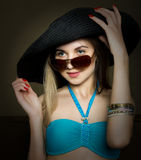 Beautiful young lady in a bathing suit, big black hat on high heels, and sunglasses Stock Photography