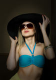 Beautiful young lady in a bathing suit, big black hat on high heels, and sunglasses Royalty Free Stock Images